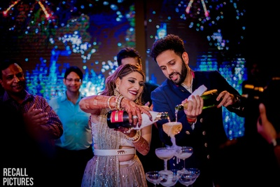 The bride and groom pouring champagne at their sangeet