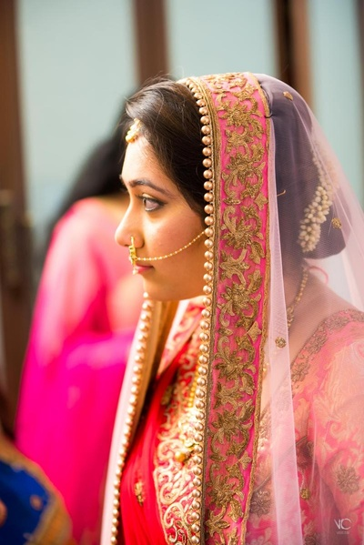Bride looking extremely beautiful in this pinkish red lehenga with golden zardozi work for her wedding