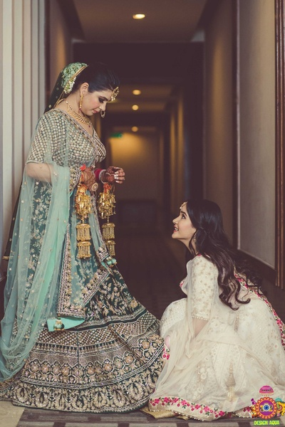 candid shot of the bride getting ready with her bridesmaid sister shiv shakti helping her