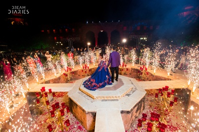 Bride and groom pose for their friends and family at their sangeet