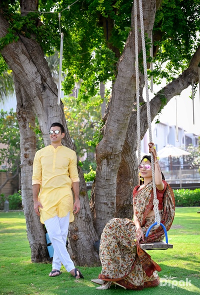 The bride enjoys herself sitting on the swing while the groom poses for a picture!