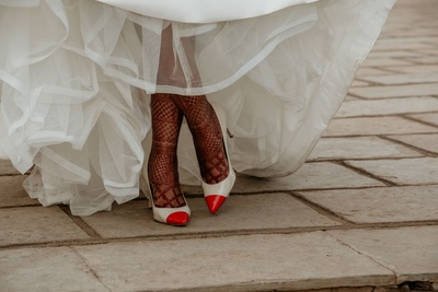 A unique shot of the bride flaunting her mehendi and heels during a church wedding.