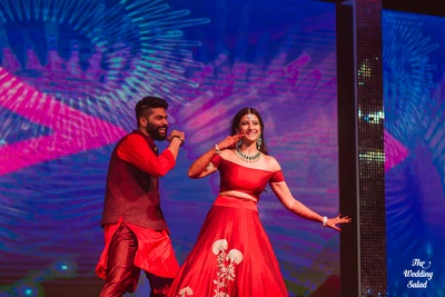 Brother and Sister duo performing at the Sangeet ceremony. Kunal wearing a red and maroon Nehru jacket
