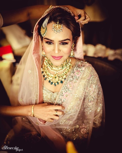 Kainaat getting ready for her reception in a blush pink lehenga