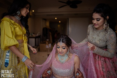 The bride getting ready for her wedding with her sisters