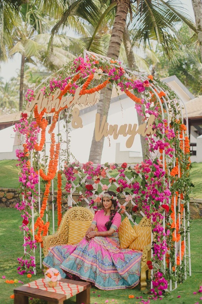 A stunning arch-like framework bedecked with flowers serves as a cozy spot for the couple to sit for the ceremony.