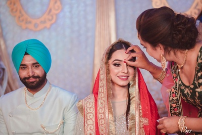 A relative applies tikka on the newly married bride as a part of the post-wedding function