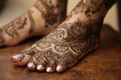Feet covered in intricately patterned mehendi designs