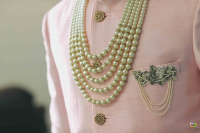 Close up shot of the groom's jewellery and brooch on top of his pink sherwani
