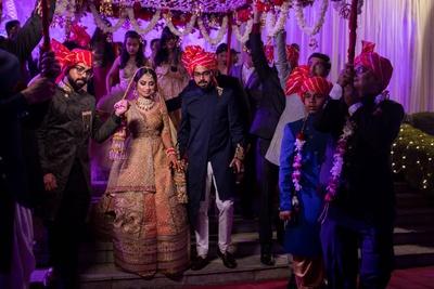 The bride entering the wedding venue under a phoolon ki chaadar.