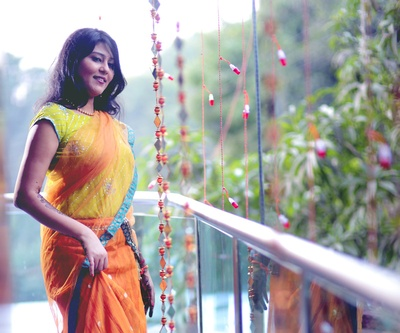 Orange lehenga with sequins buttis paired with an embellished lime green blouse and matching blue brocade bordered net dupatts