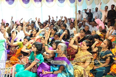 Family and friends of couple showering flowers as blessings for the newly weds