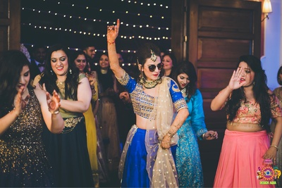 Bride's swag filled wedding pose during the sangeet function captured by Design Aqua Studio