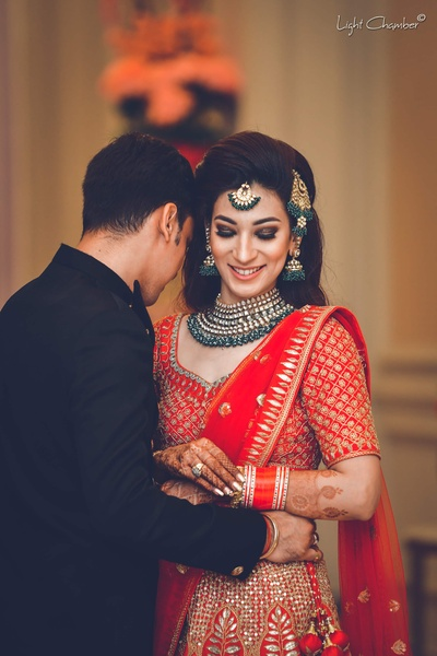 Bride and groom pose for a candid click by Light Chambers at their reception function