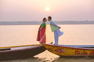The couple leaning towards one another trying to kiss, against a mesmerizing sunset view!