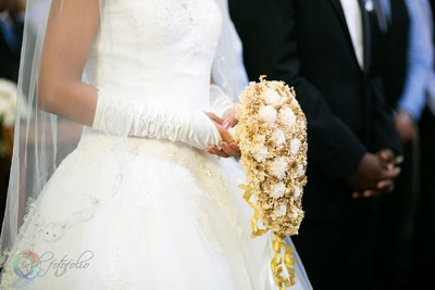 White flared wedding gown adorned with matching sheer veil, hand gloves and a white and gold flower bouquet
