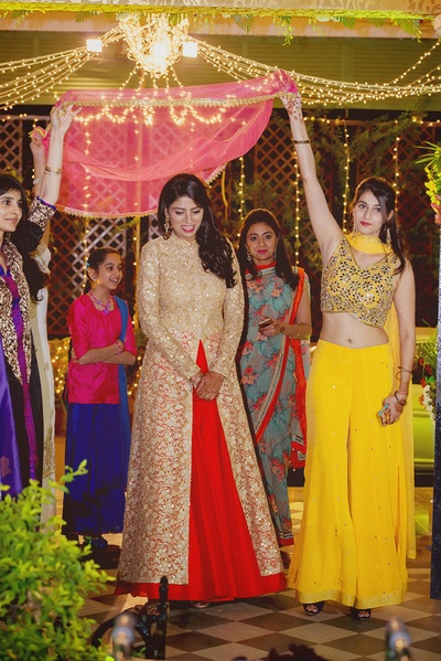 Bride Bismin wearing red and gold anarkali lehenga for the sangeet ceremony.