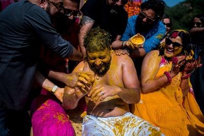 the groomsmen smearing the groom with haldi