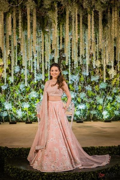 Benaisha Kharas in a blush pink lehenga with Parsi gara motif by Anita Dongre for the reception held at a traditional Parsi Agiary in Mumbai