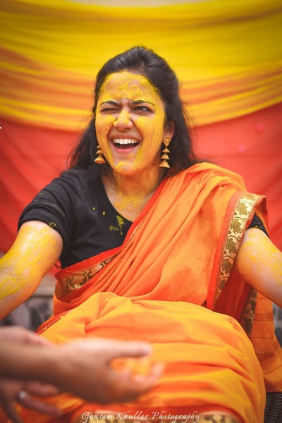 Wearing orange saree paired with black blouse for the Haldi ceremony held at Neemrana Fort Palace.