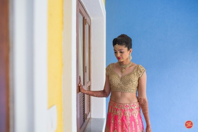 The bride in royal golden blouse and pink lehenga adorned with golden jewellery