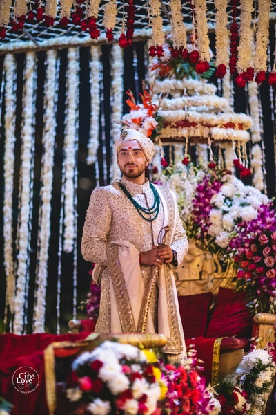 The groom looks deboanir in his cream and gold sherwani, paired with a emerald pearl necklace.