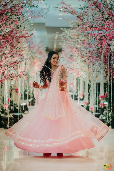 the bride twirling in a blush pink lehenga