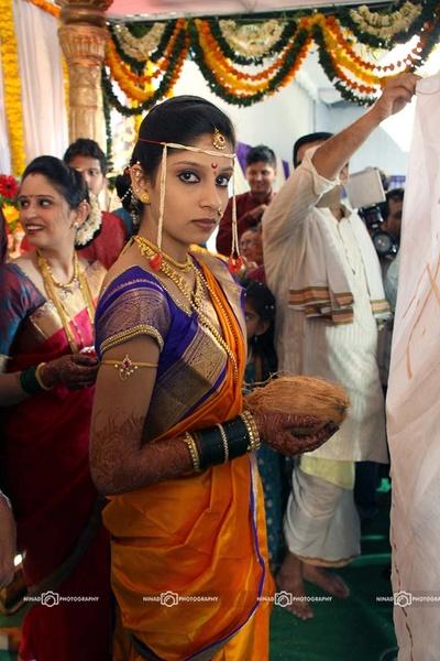 Yellow shimmer navaari silk saree styled with pearl Mundavalya