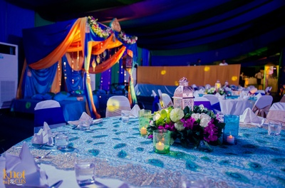 Table settings decorated with clustered flower arrangement and Moroccan style lamp and candles