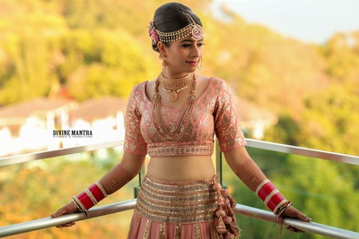 The bride donning a coral lehenga for her wedding