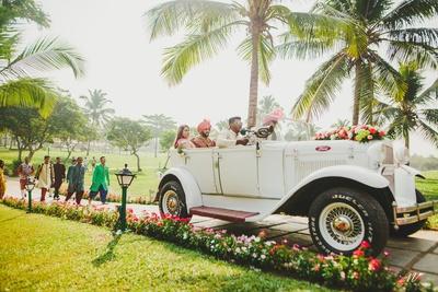 the groom entering his wedding in a vintage car