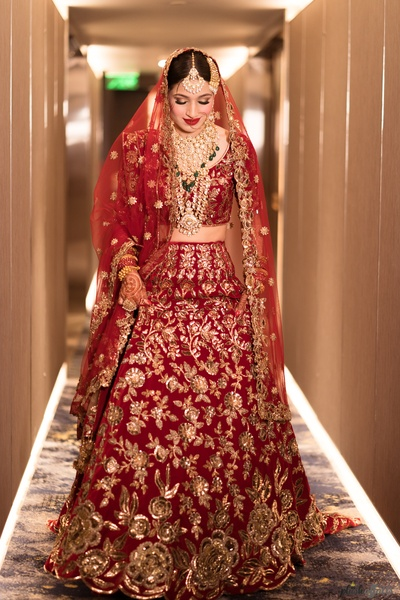 The bride looks like a million bucks in this traditional red heavily embellished lehenga.