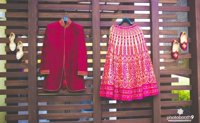 Red jacket sherwani for him and pink wedding lehenga for her, styled with matching mojris and gold stilletoes