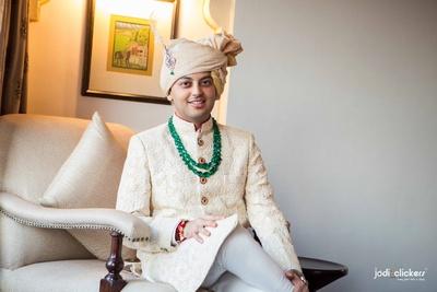 Buttery yellow wedding sherwani embellished with white resham embroidery, green emerald haar, kalgi adorned gold Safa