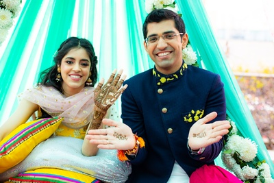 The couple show off their mehendi designs.