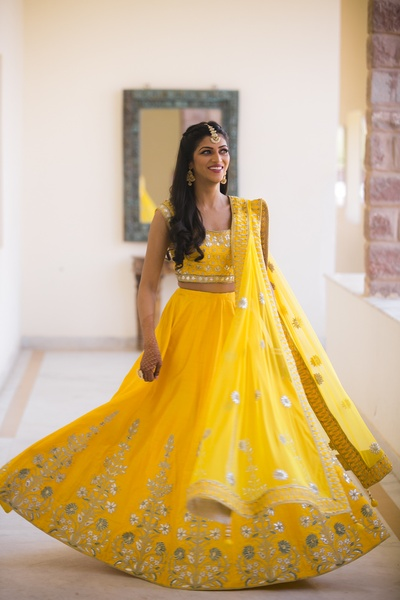 The bride looks stunning in a bright yellow lightly embellished lehenga at her meehndi ceremony.
