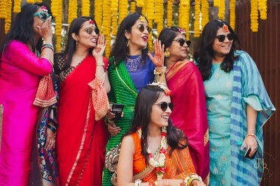the bride and her bridesmaids teasing the groom at the haldi ceremony