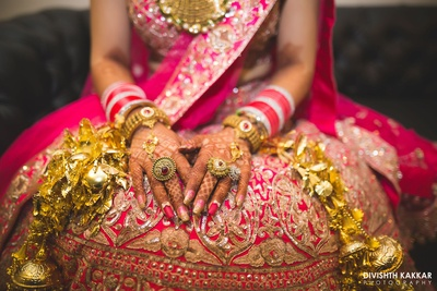 Bridal hands adorned with gold heavy kaleere and gorgeous rings.