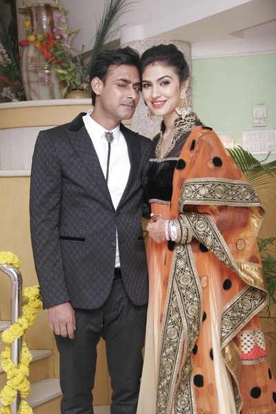 The couple is urbanely dressed in anarkali lehenga and black suit