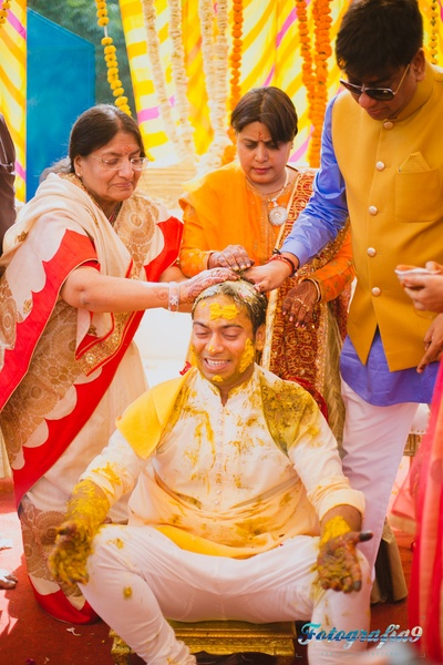 Groom dressed in an all white outfit for the haldi colors to stand out
