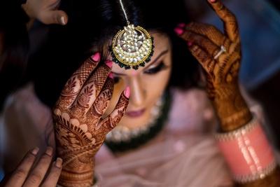 the bride wearing a chandbali maantika for the wedding cermony