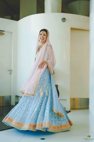 Bride twirling in her powder blue lehenga with gold trimmings