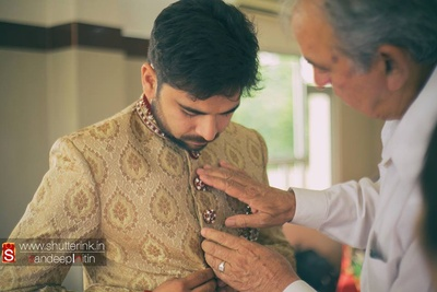 Beige textured sherwani embellished with white and red 3d button details