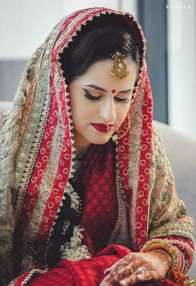 Bridal portrait of Kanika in her red lehenga and contrast smokey eye and bridal makeup look