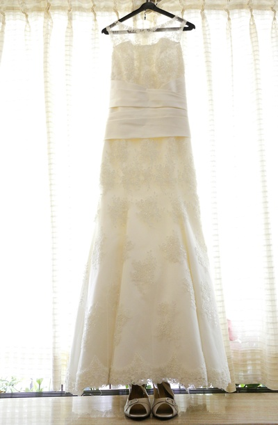Beaded and embroidered a-line white wedding gown with a scalloped lace hemline and a sheer lace neckline