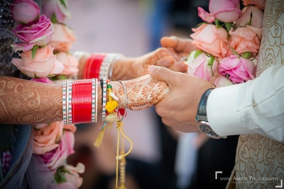 A close-up shot of the bride and groom holding hands during the wedding ceremony.