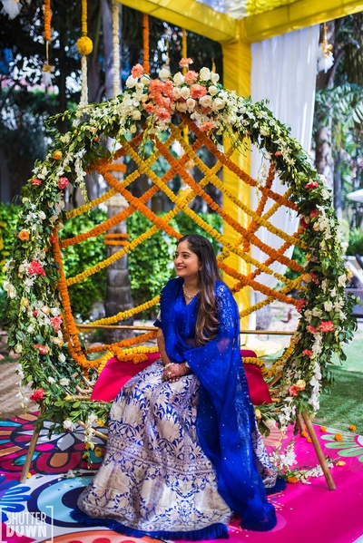 bride in her mehndi lehenga sitting on a beautiful floral jhula