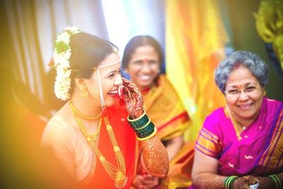 Bride is wearing a choker, necklace, Mohanmala with a pendant, earrings, maangtikka and green glass bangles