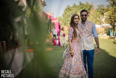 Bride wearing a Rahul Misra lehenga for her mehendi matching the groom's jacket