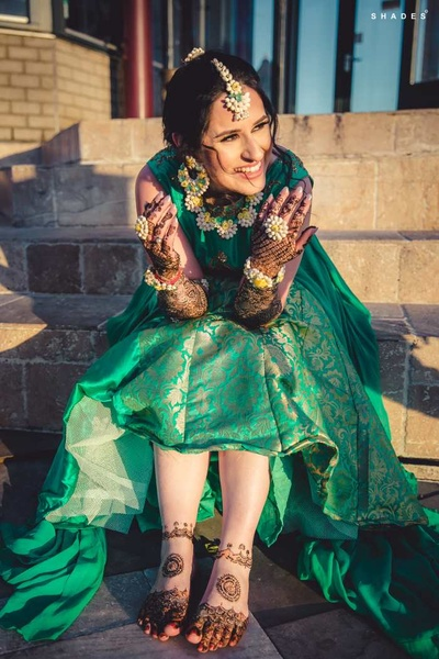 Bride poses in her green lehenga showing off the mehndi design for hands and feet